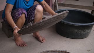 Peasant Poor Woman Farmer Sifts Rice In Asian Village