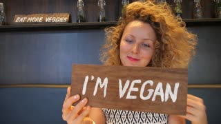 Pretty Young Woman Posing with Vegan Sign. Healthy Eating Concept. Dieting.
