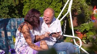 Senior Couple Using Digital Tablet in Summer Garden