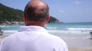 Senior Retired Man On Beach Looking at Sea