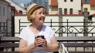 Senior Woman Holding Takeaway Coffee Cup Resting Outdoors
