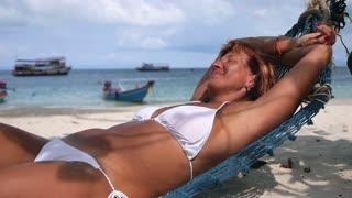 Senior Woman Relaxing On Beach in Hammock