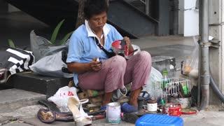 Senior Woman Shoemaker At Sideway. Poor People In Asia Work Hard To Earn Money.