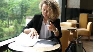 Tired Female Employee With Documents In Cafe
