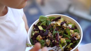 Top view of woman eating healthy delicious salad with fork. Vegan salad with lots of greens, leaves, beetroot, tofu and avocado. Healthy life style concept.