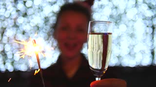 Woman Celebrating Christmas Holding Champagne And Sparklers