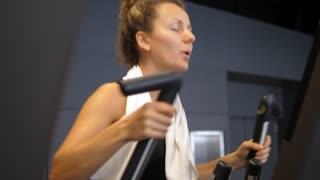 Woman Exercising on a Cardio Machine In Gym