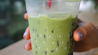 Woman Hand Holding Matcha Green Tea With Soy Milk
