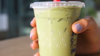 Woman Hand Holding Vegan Matcha Green Tea Latte With Soy Milk