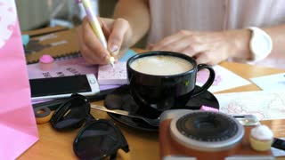 Woman Hands With Pen Writing Note with Coffee In Cafe