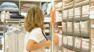 Woman Shopping In Mall Choosing Bed Sheets