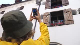 Woman Tourist Taking Photos With Smartphone Of Historic Building While Sightseeing In City