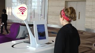 Woman Traveler Scanning Passport To Use Free WiFi In Airport
