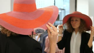 Woman Trying On Summer Hat In Clothing Shop In Front Of Mirror