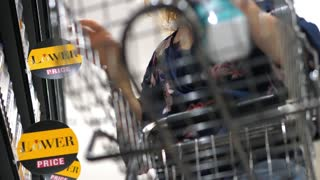Woman With Shopping Trolley Buying Products In Supermarket