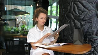 Young Woman Choosing Food In Menu In Restaurant