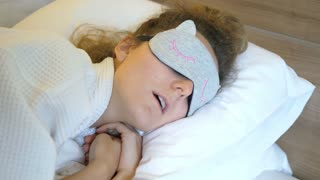 Young Woman In Sleeping Mask In Bed