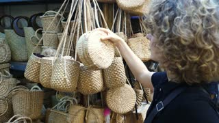 Young Woman Shopping For Trendy Wicker Bag On Market