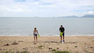 Volunteer Couple Collecting Garbage and Cleaning Beach.