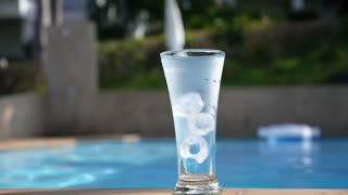 Water Flowing into Glass with Ice near Swimming Pool. Slow Motion.