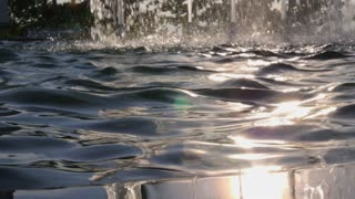 Water Surface with Sun Reflection in Fountain with Splashing Stream
