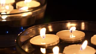 White Candles Floating on Water in Bowl at Night.