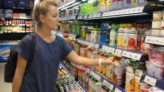 Woman Buyer Choosing Juice in Grocery Store