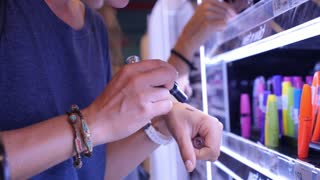 Woman Buying Cosmetics in Supermarket. Applying Lipstick