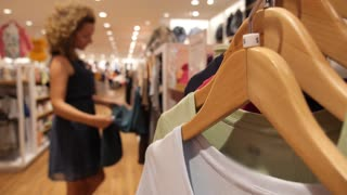 Woman Choosing Clothes in Shopping Mall