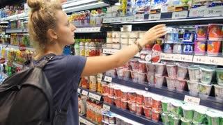 Woman Choosing Dairy Yoghurt in Supermarket