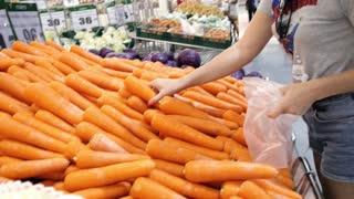 Woman Choosing Healthy Carrot Vegetable in Supermarket