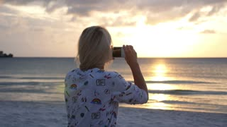 Woman Hands Taking Picture with Mobile Phone at Sunrise