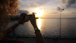 Woman Hands Taking Picture with Mobile Phone at Sunset