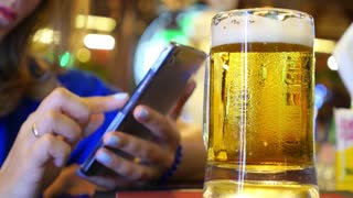 Woman Hands Use Smart Phone in Bar with Beer