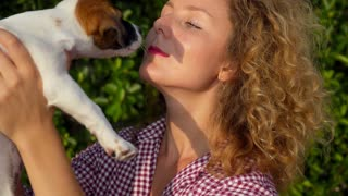 Woman Hugging and Kissing Cute Small Puppy Outdoors.