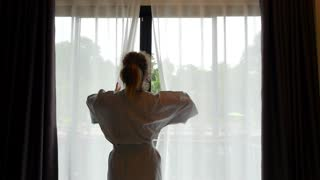 Woman in Bathrobe Opening Window Curtains at Hotel Room