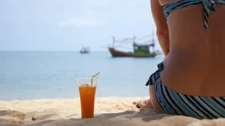 Woman in Bikini with Fruit Shake Relaxing on Beach