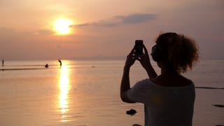 Woman in Earphones Taking Picture with her Smartphone at Sunset