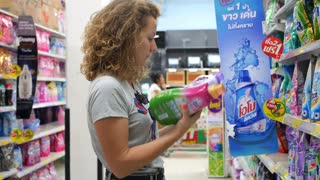 Woman in Supermarket Choosing Goods