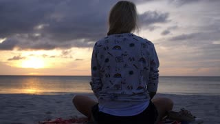 Woman in Yoga Lotus Meditation Position on Beach at Sunrise