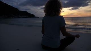 Woman in Yoga Lotus Meditation Position on Beach by Sea