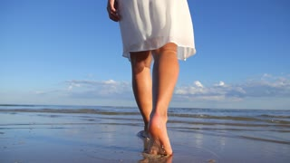 Woman Legs Walking on Beach with the Sea Water