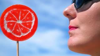 Woman Licking Red Lollipop. Closeup.