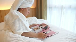 Woman Lying in Bed while Reading Fashion Magazine