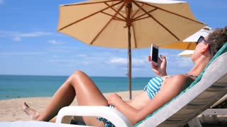 Woman on Beach Using Smart Phone on Vacation