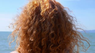 Woman Playing with Her Curly Red Hair and Relaxing on the Beach. Slow Motion.