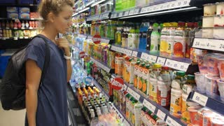 Woman Reading Information on Label about Juice in Shop