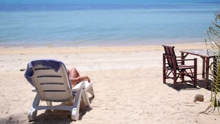 Woman Relaxing on Beach on Chaise Lounge on Holidays