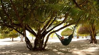 Woman Resting in Hammock on a Beach near the Sea.