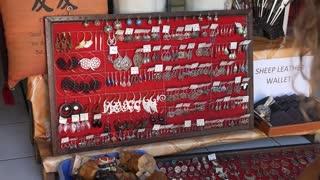 Woman Shopping Choosing Ethnic Earrings in Jewelery Store